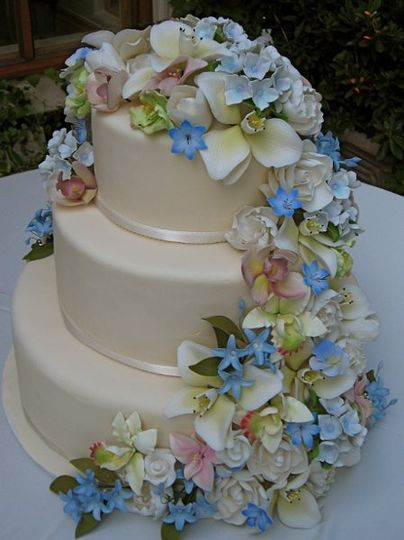 A simple 3 tiered fondant covered cake with a heavy cascade of mixed, sugar florals