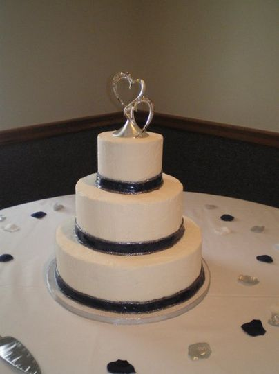 round tiered buttercream wedding cake with fondant ribbon.