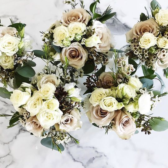 Bridesmaid bouquets featuring white and champagne blooms