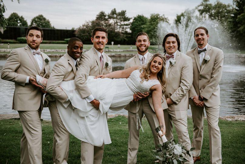 Groomsmen carrying the bride