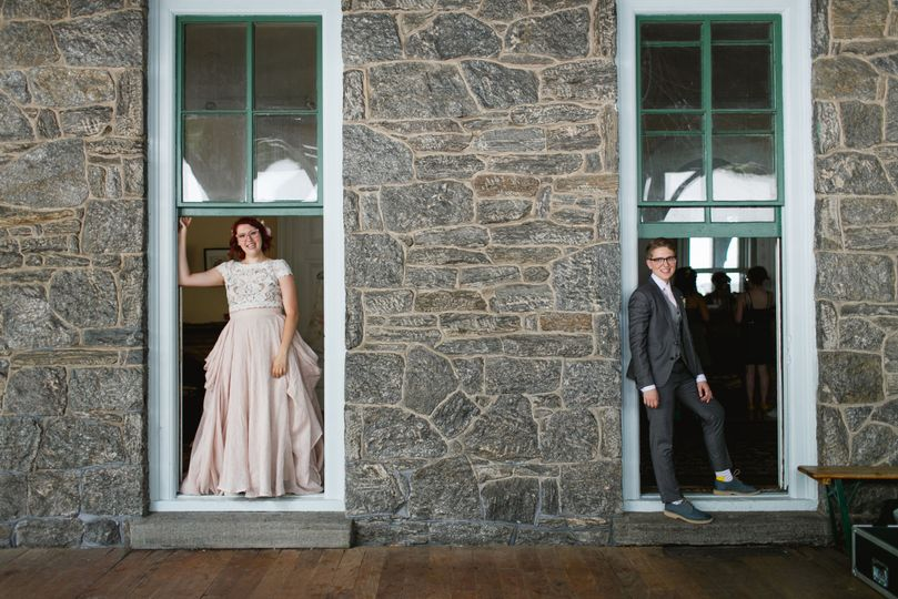 Bride and groom standing on the window sills