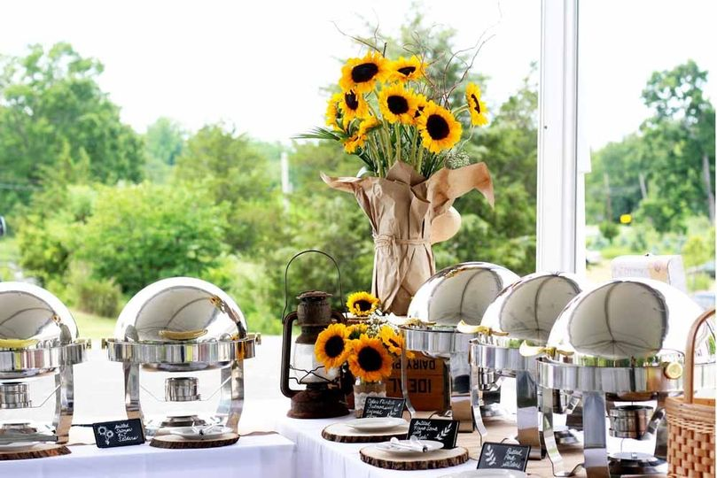 Buffet with vintage lanterns and sunflower floral arrangements to match the bride's decorations