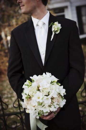 Groom holding his bride's bouquet
