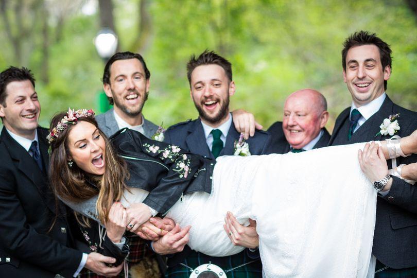 Groom and groomsmen carrying the bride