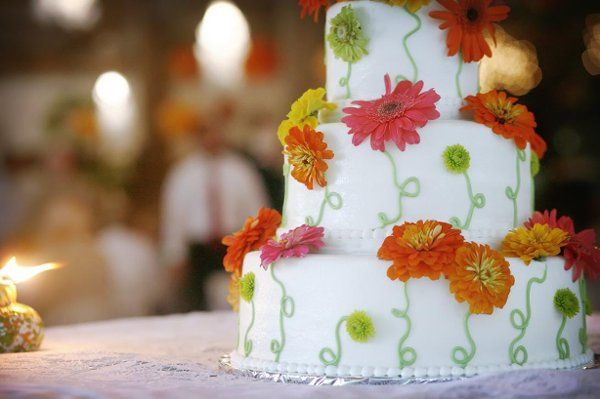Fresh zinnias have been placed on the cake. Cake severs 126