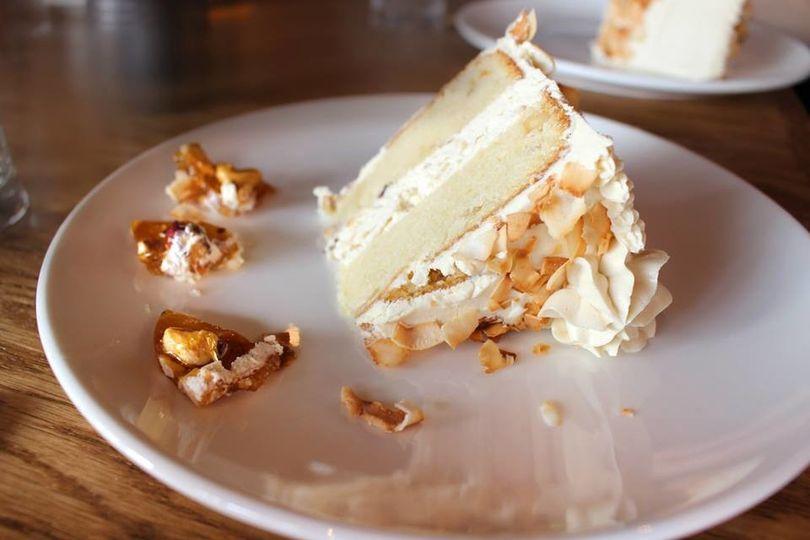 Slice of macadamia nut cake with espresso Italian buttercream, chopped hazelnuts, toasted coconut,...
