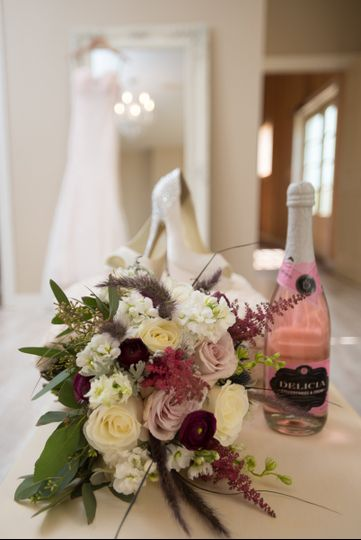 Bridal bouquet and shoes with a bottle of wine