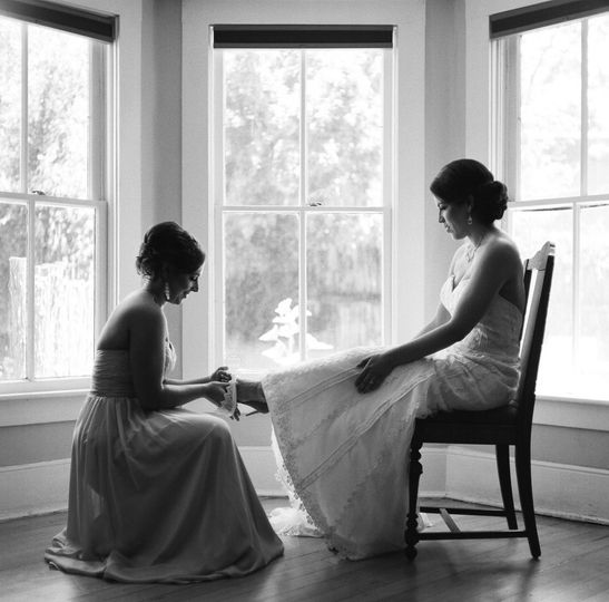 Bridesmaid helping bride with shoe