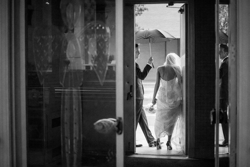 Black and white photo of bride entering rain