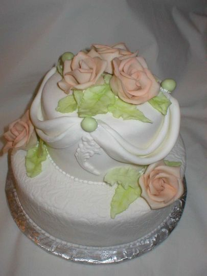 White two tier chocolate cake with pink roses.