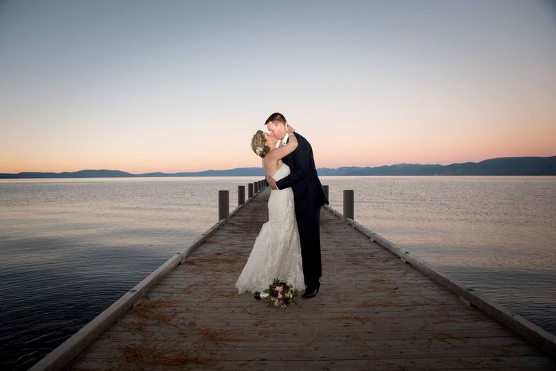 Newlyweds kissing on the dock