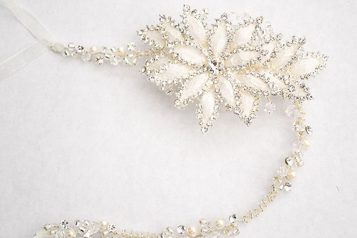 A white enameled lily flower blooms on a delicate crystal, pearl and rhinestone chain and is traced...