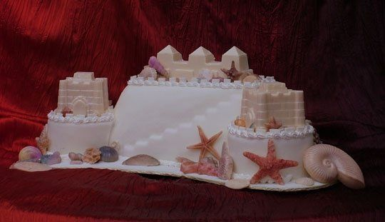 This sandcastle wedding cake if a free form design, featuring 2 white identical chocolate sandcastle...
