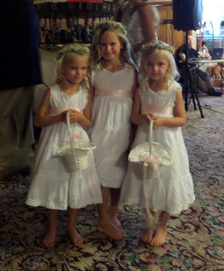 Flower girls at a summer wedding in a museum.