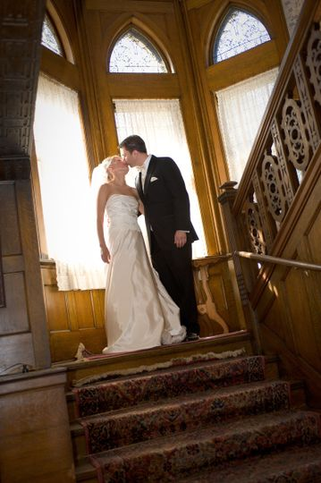 Newlyweds kiss by the staircase