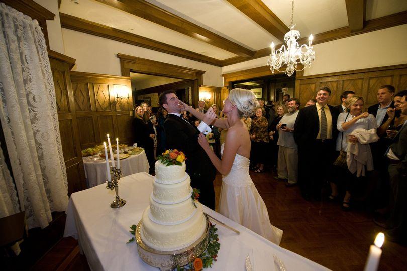 Newlyweds by their wedding cake