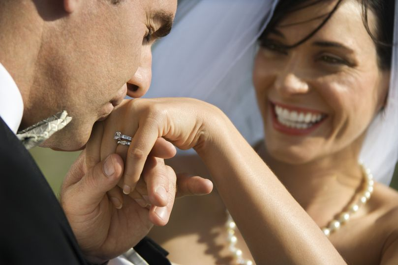 groom kissing hand of bride