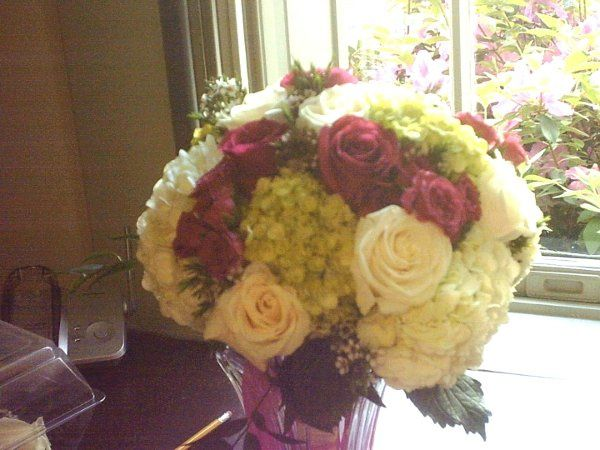 Summer garden bouquet features, pink roses, green  and white hydrangea, waxflower.