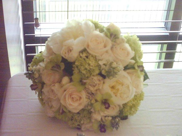 Features pink peonies, green hydrangea, white roses, green orchids, and waxflower