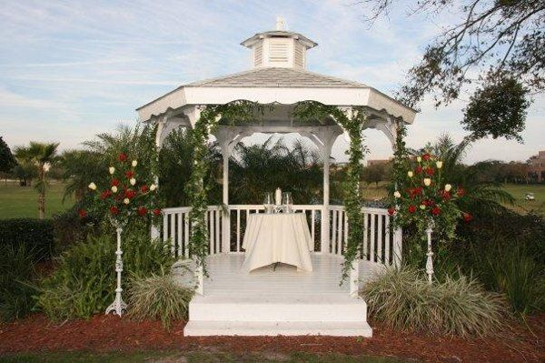 Heathrow Country Club Gazebo decorated with hanging Ivy and tall florals in white stands made with...