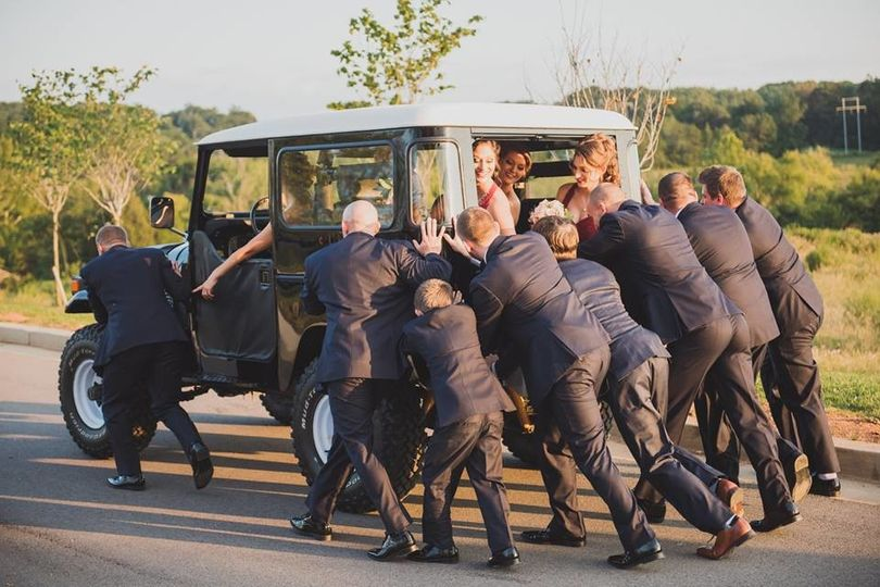 The bridesmaids direct the groomsmen in how to push the car | Sullivan Photography