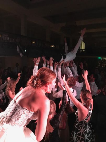 Groom crowd surfs from stage.