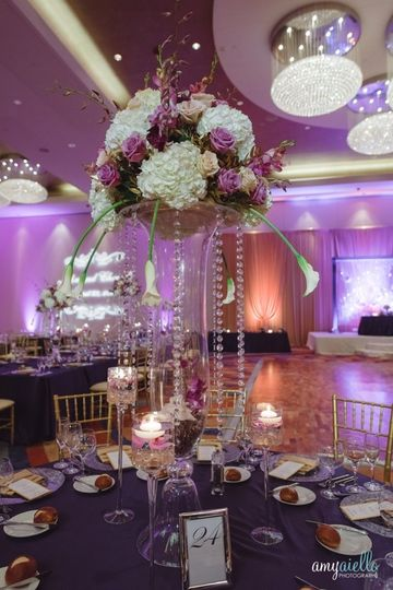 Large style centerpiece with floral, crystals, a hint of willows atop a unique glass vase