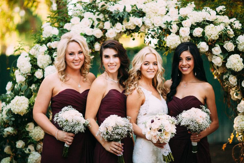 Bride and bridesmaids by the floral arch