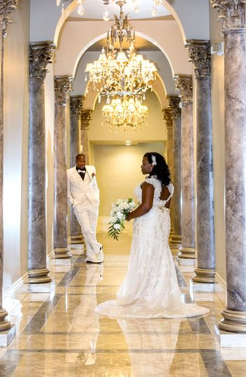 Beautiful image in the hall. Groom slightly blurred focusing on the bride. Depth of field image.