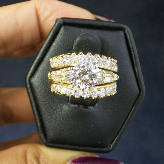 An Albert Carabet original design, set with a certifed E VS1 colorless diamond centerpiece.  18K...