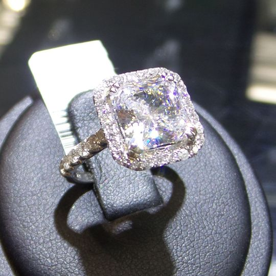 A glamorous square cut diamond gleams on fabulous halo engagment ring.   18k White Gold
