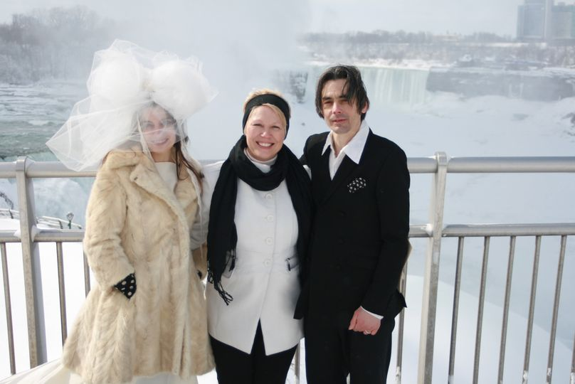 Officiant and newlyweds in the snow