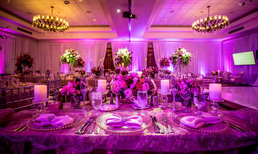 Floor to ceiling white drapery with purple uplighting