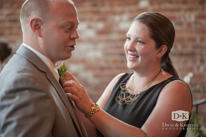 Fixing his boutonniere | Photo by David & Kristina