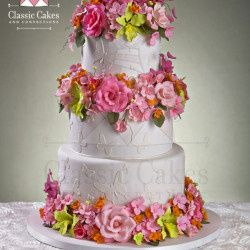 white cake with butterflys and multi color flowers