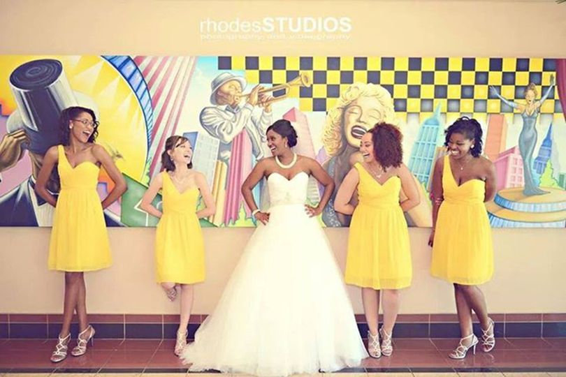 Bride and her bridesmaids by the wall art