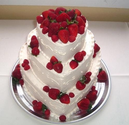 This is a heart shaped three tier with fresh strawberries and side swirls.