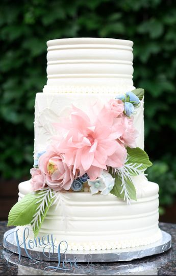 This buttercream wedding cake is adorned with handmade, edible wafer paper flowers and sugar...