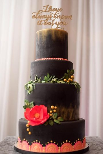A black fondant wedding cake with edible wafer paper foliage and sugar details.