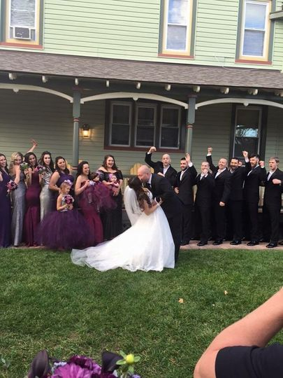 Behind the scenes photo of bride and groom, entire wedding party