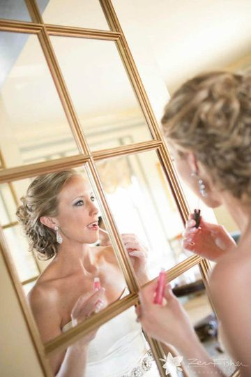 Bride doing touch ups on makeup