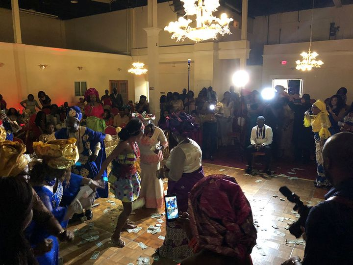 Everyone cheers as the bride performs a special, traditional Igbo dance for her groom at this...