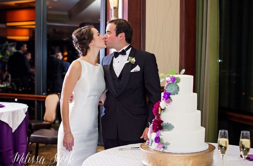 Newlyweds kiss by their wedding cake