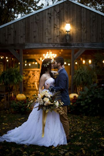 Newlyweds kissing outside the barn