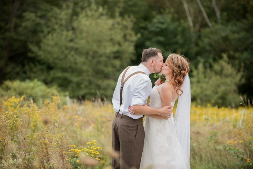 Newlyweds in a field - Kiss the Bride Photography