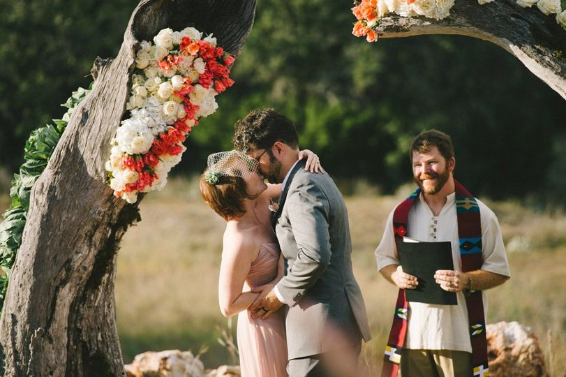 First kiss at outdoor ceremony incorporating be-flowered tree trunks on property. Photo by Nathan...