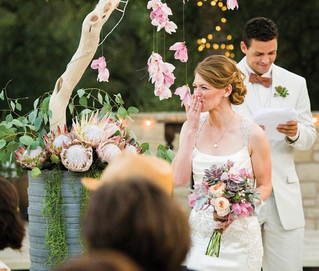 Bride blowing kiss during ceremony, holding succulent bouquet. Hanging orchid altar piece and...
