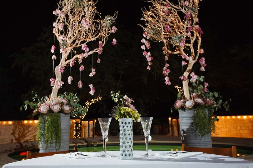 Bride and groom table with hanging orchid backdrop. Outdoor wedding in Austin, Texas. Photo by Jake...