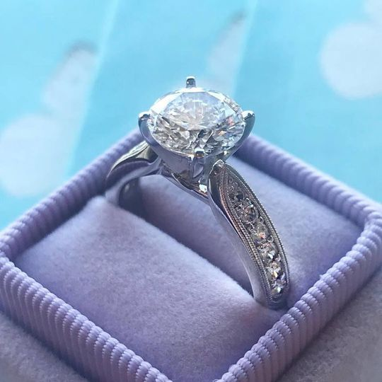 Classic round diamond with side accent diamonds in our vintage lavender heriloom box