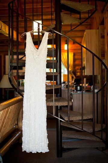 Wedding dress hanging from the stairs in the log cabin.